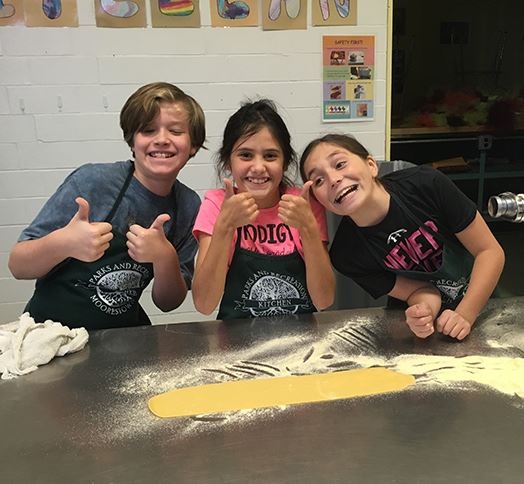 Three Children Rolling Out Pasta Dough